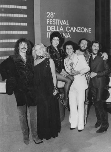 La presentadora italiana Maria Giovanna Elmi, sentada en el centro, sonríe junto a los miembros de Matia Bazar, ganadores del Festival de San Remo de 1978.